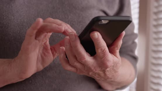 Thumbnail for Tight shot of old woman's hands texting on phone by window in domestic setting