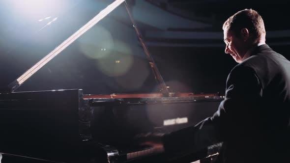Thumbnail for Pianist spielt Klassisch Klavier auf der Bühne in einem Saal mit dunklem Licht