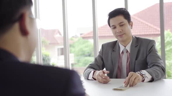 Businessman giving money while making deal to buy new house