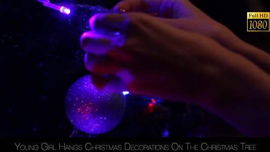 Thumbnail for Young Girl Hangs Christmas Decorations On The Christmas Tree 2