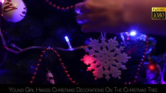 Thumbnail for Young Girl Hangs Christmas Decorations On The Christmas Tree 4