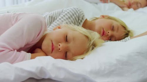 Kids sleeping on bed while parents sleeping in background 4k