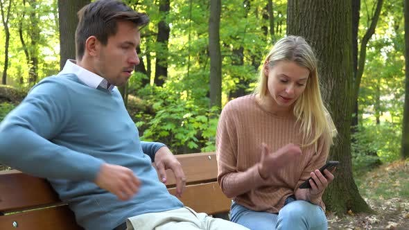 Thumbnail for A Man and a Woman Sit on a Bench in a Park and Argue About a Smartphone