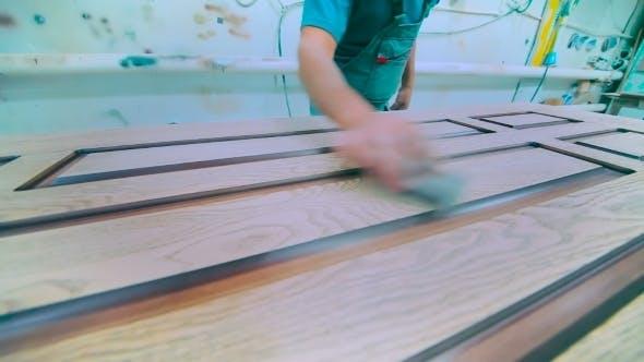 Thumbnail for Worker Carefully Polishing Door