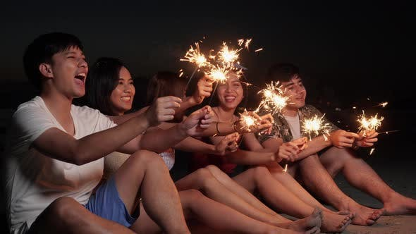 Young enjoy fireworks on beach
