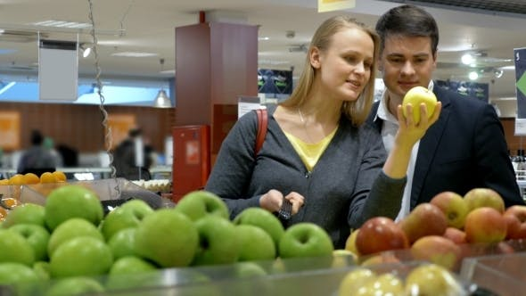 Thumbnail for Happy Young Couple Buying Apples