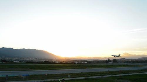 Plane Landing in Runway Airport at Sunset