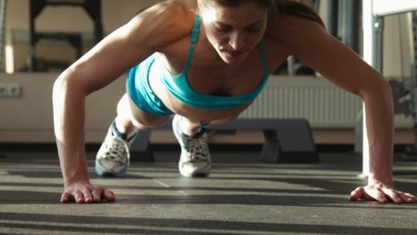Thumbnail for The Woman In Sportswear Does Push-ups In a Gym