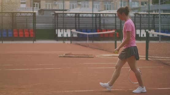 Thumbnail for A Woman Walks on a Tennis Court with a Racket and Knocks the Ball on the Ground. Concentration Will