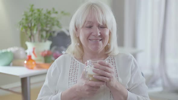 Thumbnail for Portrait of Attractive Caucasian Senior Woman with Blond Hair and Grey Eyes Drinking Coffee