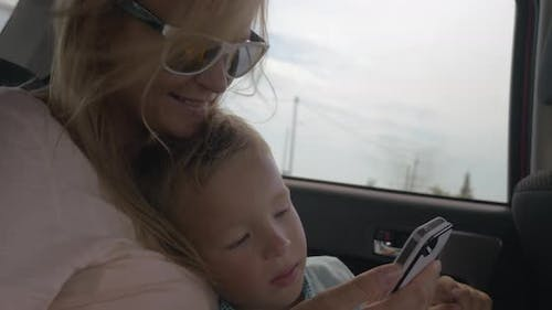 Mother and son using mobile phone during car ride