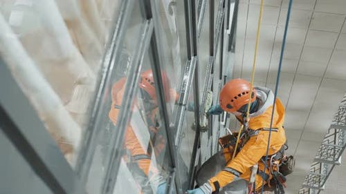 Industrial Climber in Helmet and Gloves Washes Windows on Tall Building Top View