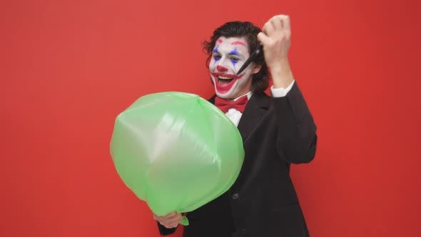 An Unusual Strange Magician Holding an Inflated Balloon on a Red Background a Magician in a Black