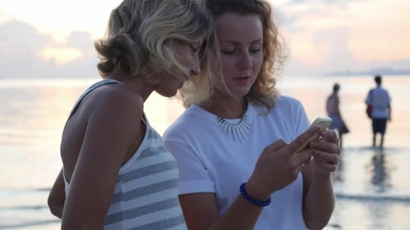 Thumbnail for Female Friends Watching Social Media On Mobile