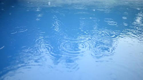 Circles of Raindrops on the Surface of the Blue Water. Abstract Background. Rain in the Swimming