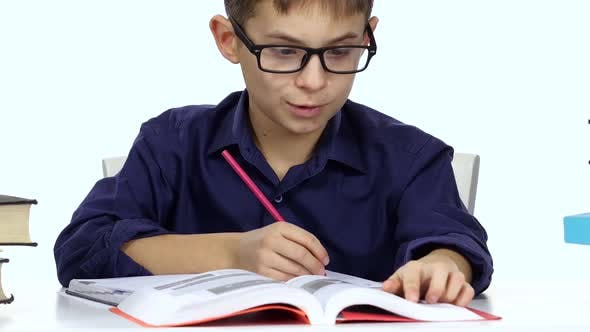Boy Sits at a Table Recording Something Into Her Notebook and Flips Through the Book. White