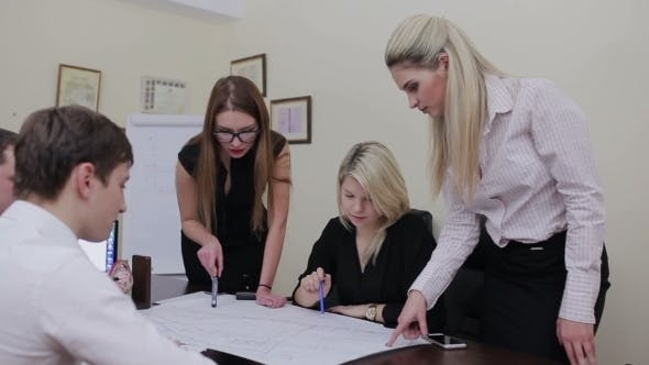 Cover Image for Architects Discussing Plans In Modern Office