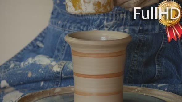Potter Craftsman in Jeans is Glazing a Pot by