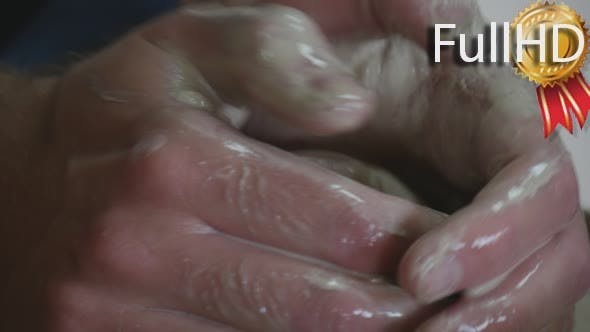 Male Potter's Dirty Hands And Wet Clay