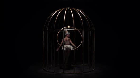 Thumbnail for Girl on Stage in a Cage Spinning on the Air Hoop. Black Background. Slow Motion