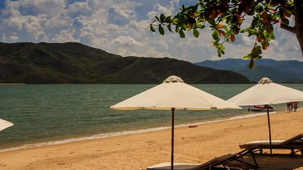 White Sunshade Parasols on Sand Beach at Azure Sea