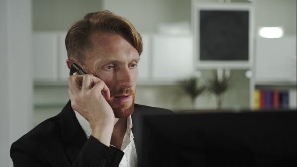 Thumbnail for Red-haired Man Sitting At a Computer And Calling