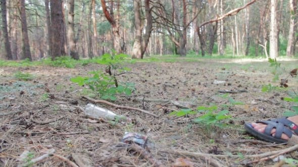 Thumbnail for Man Beats Foot Plastic Bottle In The Forest.