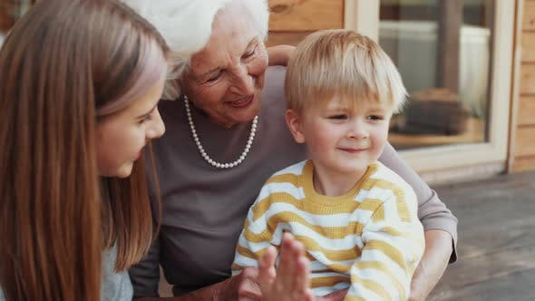 Thumbnail for Happy Grandmother Bonding with Grandkids Outdoors