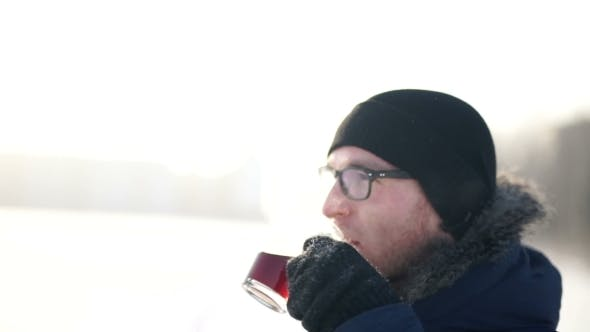 Thumbnail for Young Man Drinking Hot Coffee Outdoors In Cold