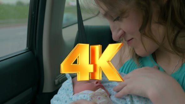 Thumbnail for Woman With Baby In Arms Riding a Car