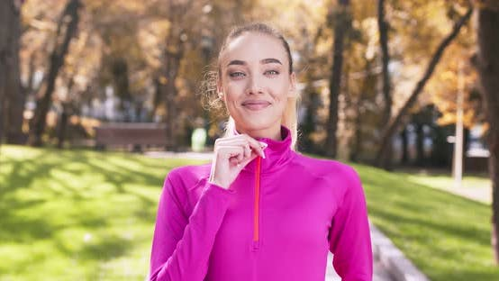 Thumbnail for Positive Blonde Woman Locking Zipper on Her Pink Sportswear and Smiling To Camera