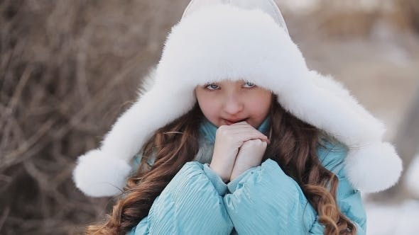 Cover Image for Cute Girl In Winter Warms The Hands Of The Park