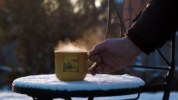 Cover Image for Cup With Hot Tea On a Snow-covered Chair