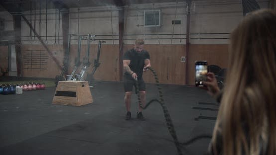 Muscular Man Using the Ropes Inside the Gym While His Girlfriend Taking Pictures