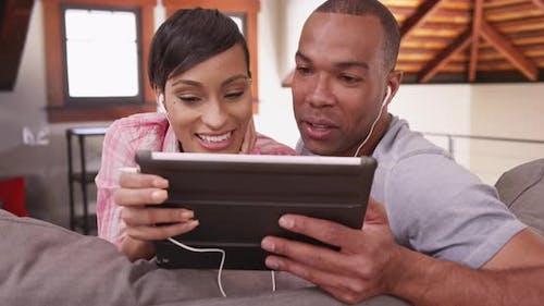 Ein schwarzes Paar sieht ein Video auf ihrem Tablet