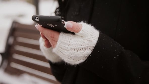 Cover Image for Young Woman In Winter Park Talking Mobile Phone