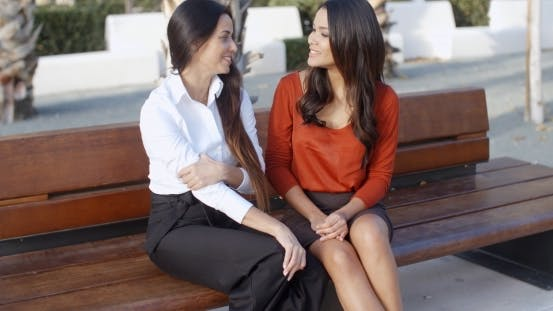 Thumbnail for Female Friends Sitting Chatting In An Urban Square