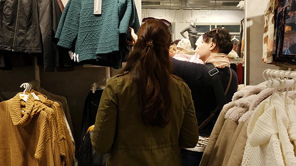 Thumbnail for Women With Baby Choosing Clothes During Shopping