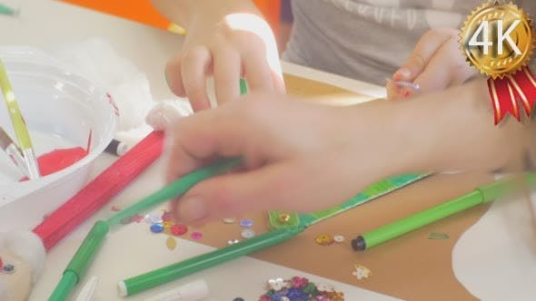 Thumbnail for Kids Hands Are Decorating a Triangle With Beads