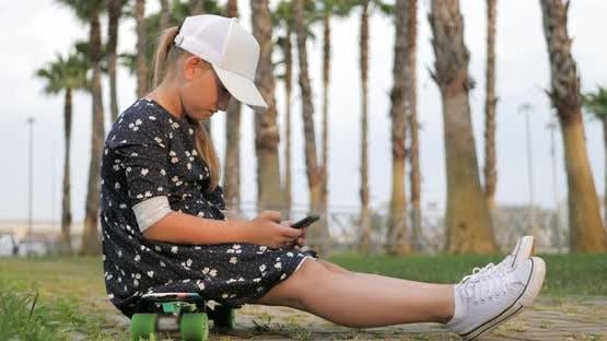 Girl Riding on Skateboard in Tropical Park