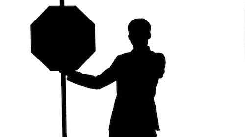 Silhouette A Businessman Holding a Stop Sign On