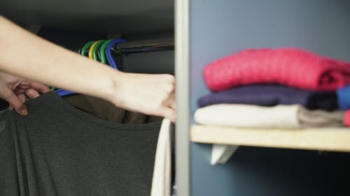 Clothing Hanging On Hangers At Wardrobe