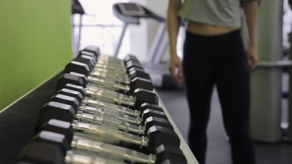 Thumbnail for Athlete Woman Chooses Dumbbells With a Shelf In Gym.