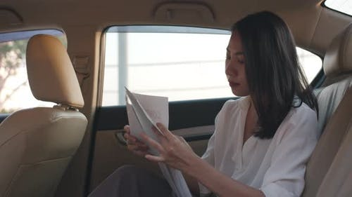 Businesswoman in fashion office clothes working in sitting back seat of car in urban modern city.