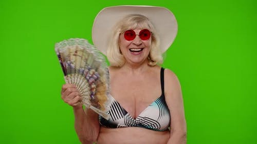 Elderly Woman Tourist in Swimsuit Bra Exhales From Heat or Stuffiness Waves Hand Fan at Herself