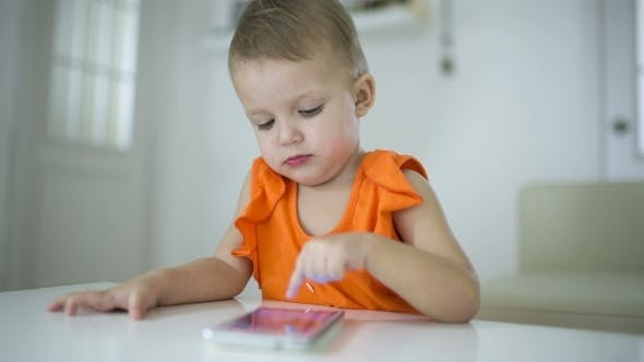 Cover Image for Young Child Plays On A Modern Smartphone In The Interior