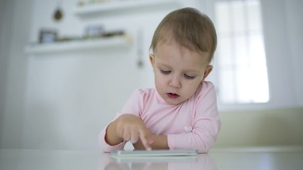 Thumbnail for Young Child Plays On A Modern Smartphone In The Interior