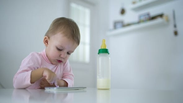 Thumbnail for Young Child Plays On A Modern Smartphone And Sucking A Bottle Of Baby Food In The Interior