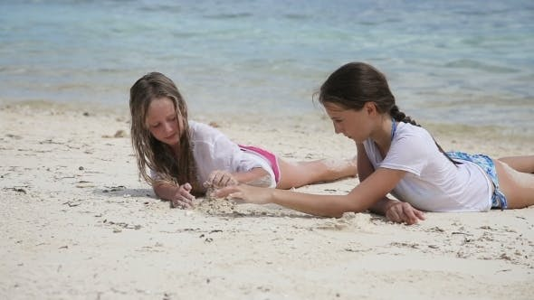 Thumbnail for Happy Girls Playing With Sand on Beach in Summer.