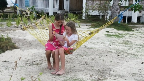 Thumbnail for Girls In The Hammock With The Tablet On The Beach